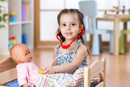 53851945 - kid girl playing doctor role game examining her doll using stethoscope. child sitting in playroom at home, preschool or kindergarten