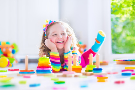 39757266 - child playing with wooden toys at preschool. cute toddler girl having fun with toy blocks, building a tower at home or day care. educational kids toy for nursery or kindergarten.
