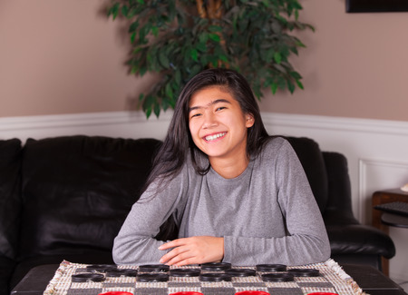 62589644 - biracial teen girl sitting at checkers board, ready to play a game with large red and black checker  pieces