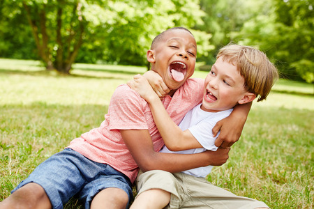 71633983 - two boys have fun in the park and wrestle while laughing